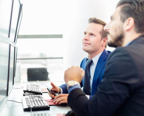 Zwei Männer analysieren Daytrading Chart
